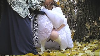 Bride struggles with her wedding dress as she pees in the woods