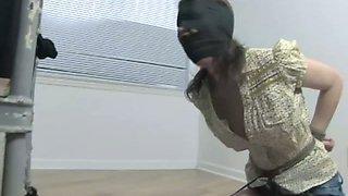 Masked slender brunette with her hands tied behind her back sucks dick